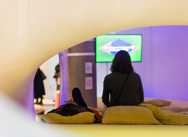 Two people sitting on cushions watching a film in an exhibition space.