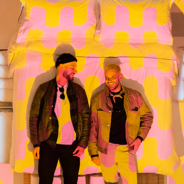 Two people stand in front of an image of a bed with graphic pink and yellow bedding.
