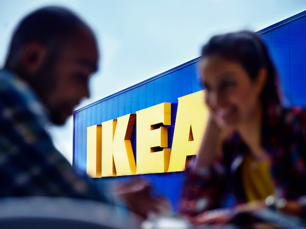 Two people talking with an IKEA store in the background. The store shows the IKEA logo which is yellow and blue, like the Swedish flag.