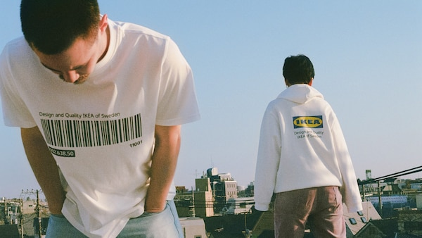Two people wearing a t-shirt and hoodie from the EFTERTRÄDA limited collection on a rooftop