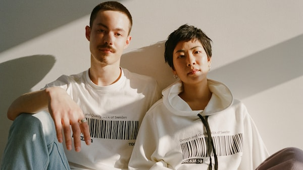 Two people wearing a t-shirt and hoodie from the EFTERTRÄDA limited collection