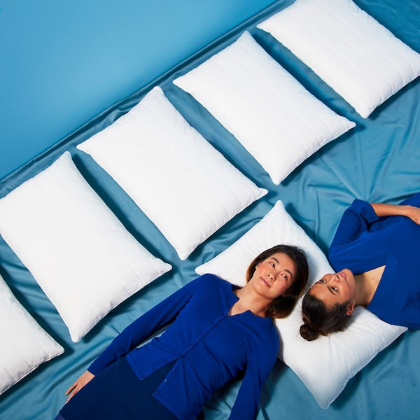 Two people wearing dark blue clothes lie on a blue floor with their heads on a pillow, beside a row of other pillows.