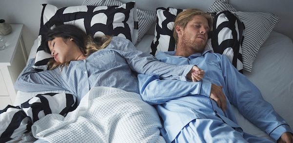 Two people wearing pajamas sleeping in a bed