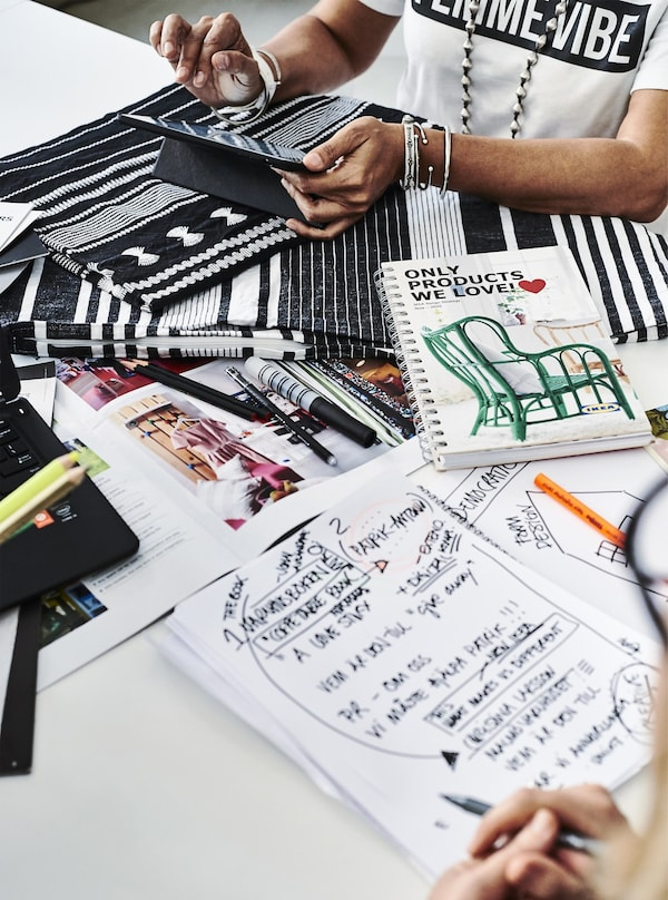 Two people working with fabric and notepads at a desk.