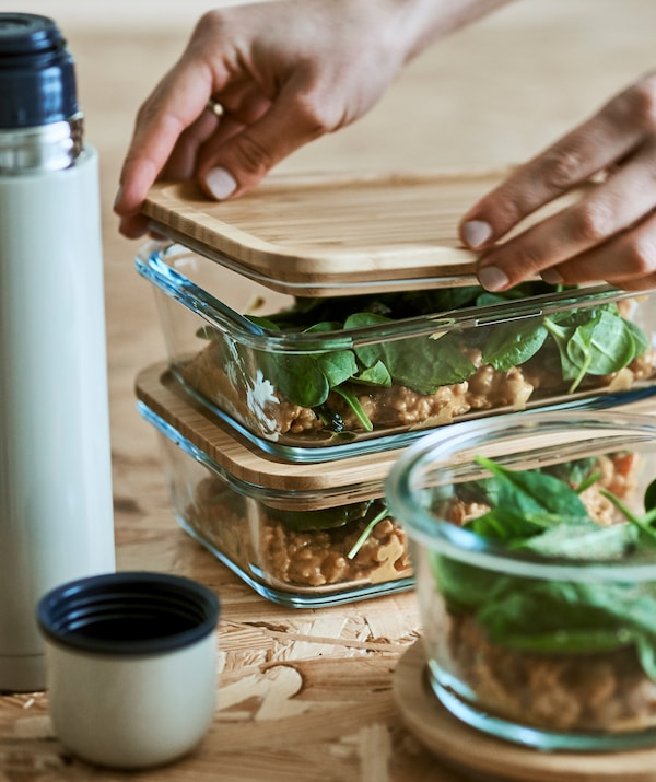 Two piles of glass food containers and a vacuum flask on a wood surface. Hands fit a bamboo sealable lid onto one glass tub.