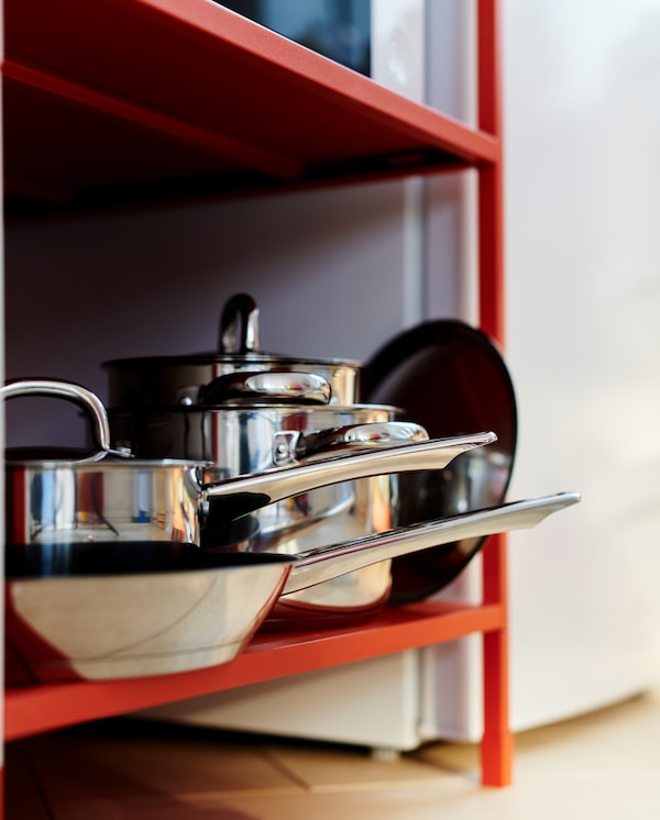 Two pots, one saucepan, one frying pan and lids in stainless steel are stored on the bottom shelf on a red shelving unit.
