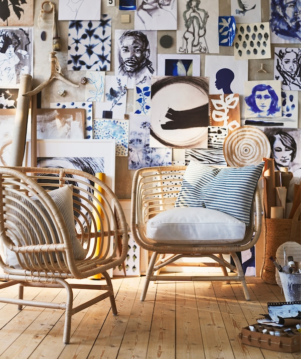 Two rattan armchairs in front of a wall covered in artwork.