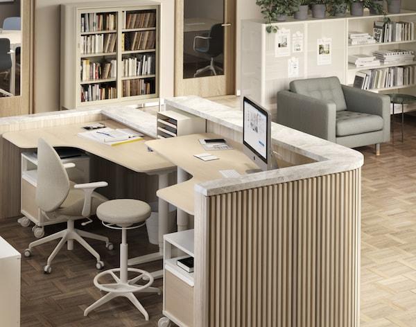 Two reception corner desks behind a half-wall wooden panel.
