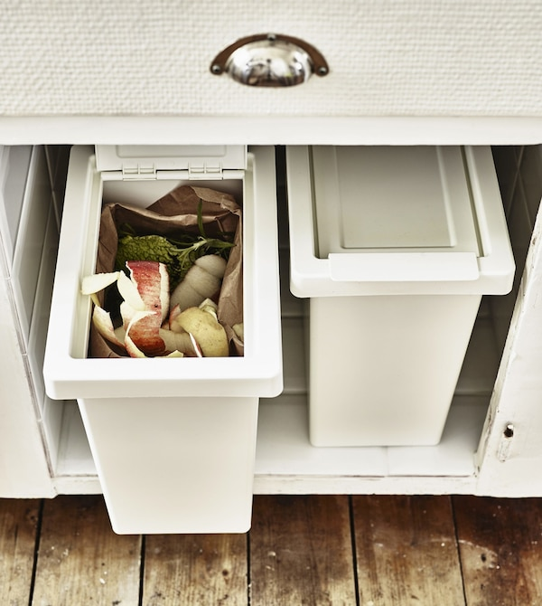 Two recycling boxes inside a kitchen cupboard.