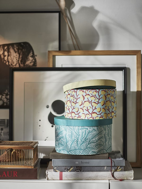 Two round storage boxes stacked on top of eachother with frames in the background