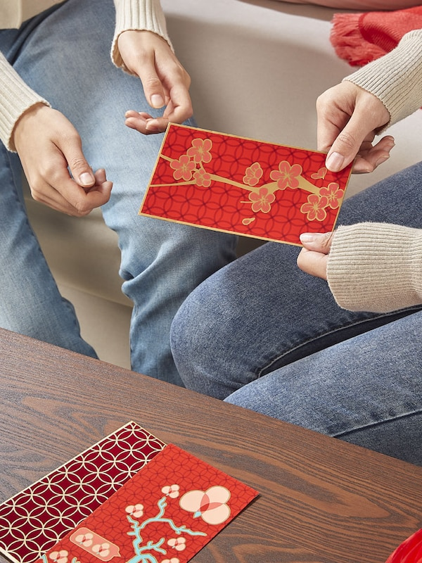 Two sets of hands exchanging a red money pouch