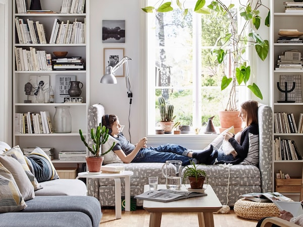 Two sisters sitting in modular sofa units, facing each other in between a pair of white bookcases.