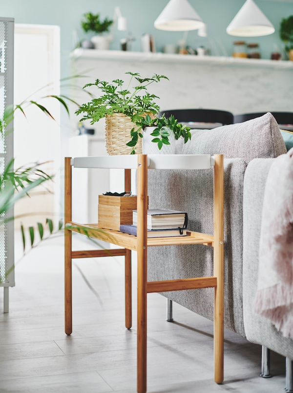 Two small, potted plants along with very light storage on a SATSUMAS plant stand placed next to a living-room sofa.