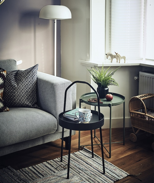 Two small, round side tables next to a sofa in a living room.