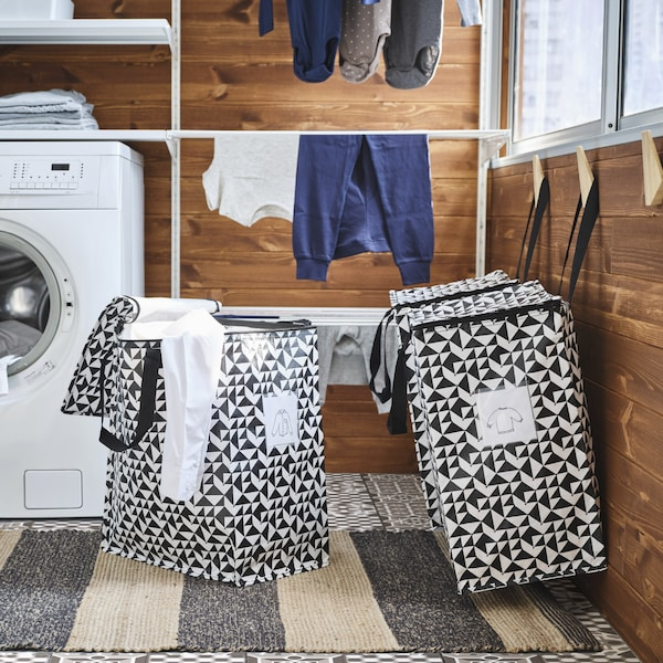 Two spacious bags in graphic design hang on wooden hooks. One more bag stands on the floor, and a white shirt hangs out.