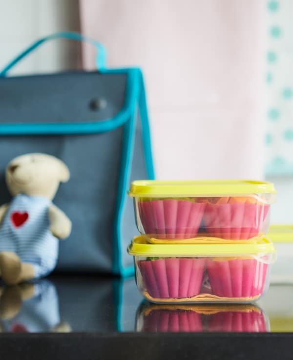 Two stacked glass food containers with yellow lids, containing pink muffin cups, near a school bag on a worktop.