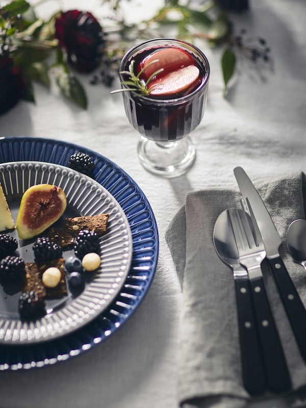 Two stacked STRIMMIG plates with berries and figs, set on a grey tablecloth beside a wine goblet, napkin and cutlery.