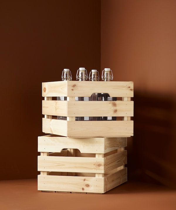 Two storage boxes made out of slats of solid wood stacked on top of each other; the upper partly filled with glass bottles.