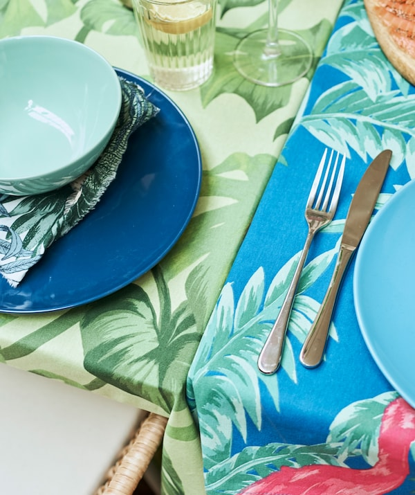 Two tables pushed together, one covered in a green leaf tablecloth, one with blue patterned fabric, each set with plates.