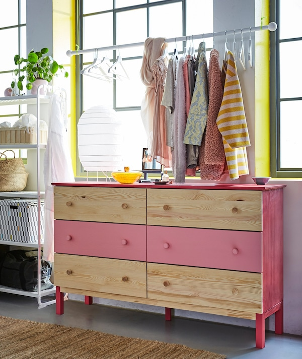 Two TARVA solid wood chest of drawers, with the middle drawers painted pink. Clothes hang above on a rod.