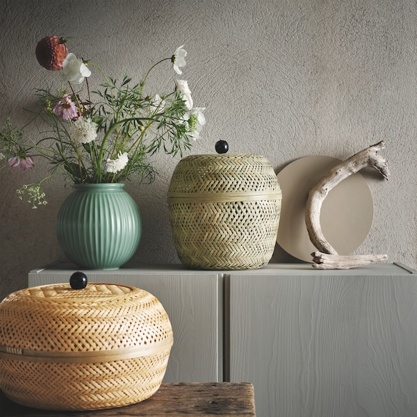 Two TJILLLEVIPS baskets in bamboo with lids are seen beside a green vase with flowers and wooden branches.