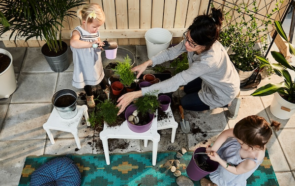 Two toddlers and a parent putting dirt into plant pots