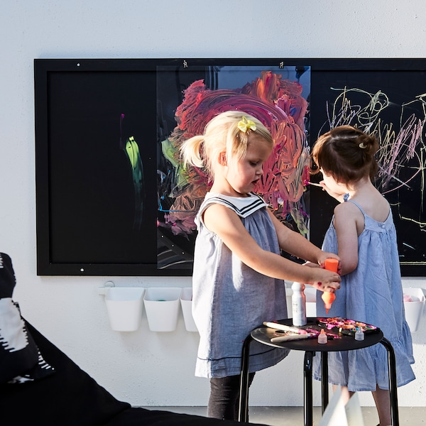 Two toddlers squeezing paint onto brushes and playing with chalk and a close-up showing the child's art being placed into a plastic frame