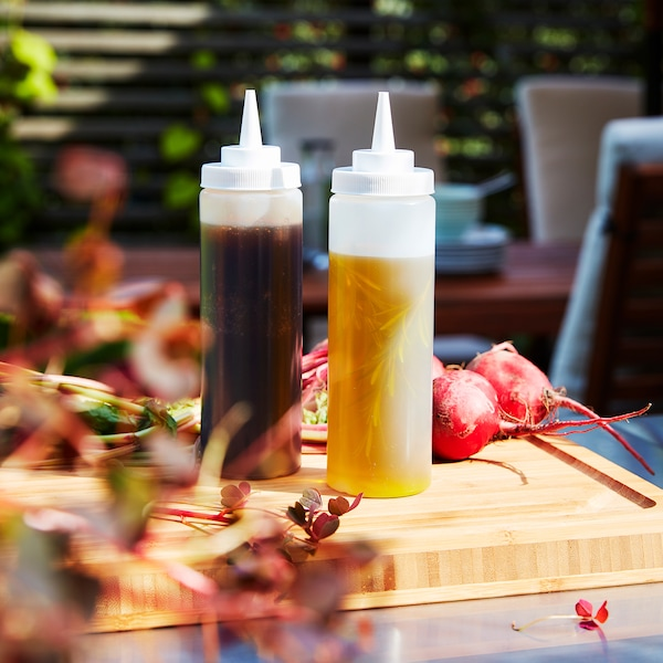 Two transparent squeeze bottles stand on a wooden chopping board. There's oil in one bottle and marinade in the other.