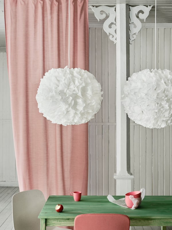 Two VINDKAST pendant lamps in a white pompom shape hanging over a green table with a pink curtain in the background.