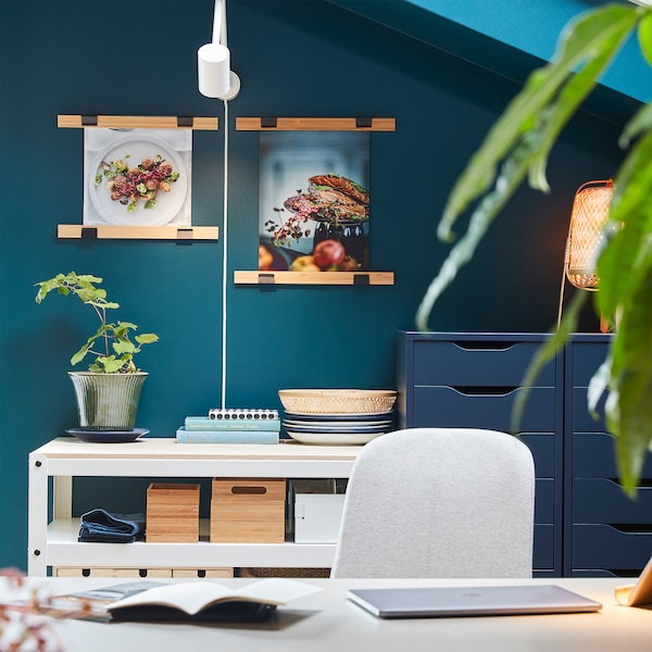 Two VISBÄCK poster hangers in bamboo with food posters hang on a wall, and a white wall lamp illuminates them nicely.
