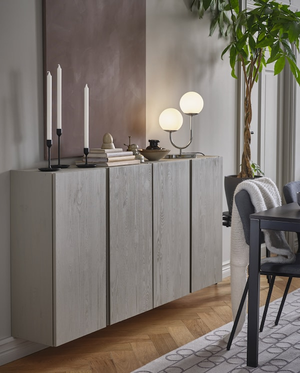 Two wall-mounted and grey-painted IVAR cabinets with candles, books, decorations and a chrome-plated table lamp on top.