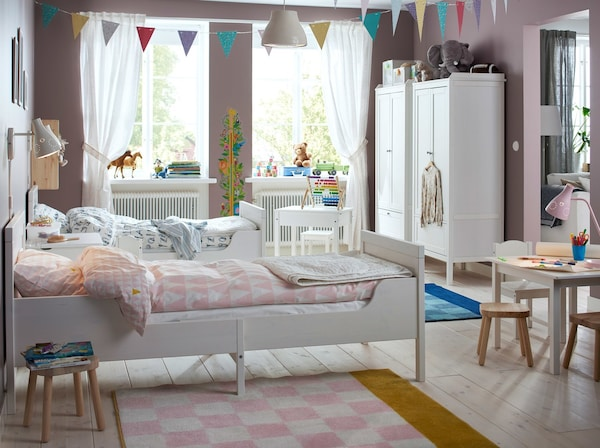 Two white extended children's beds side by side in a pink and white bedroom.