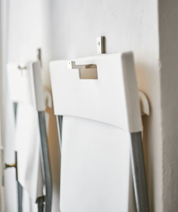 Two white folding chairs hanging from hooks on a wall.