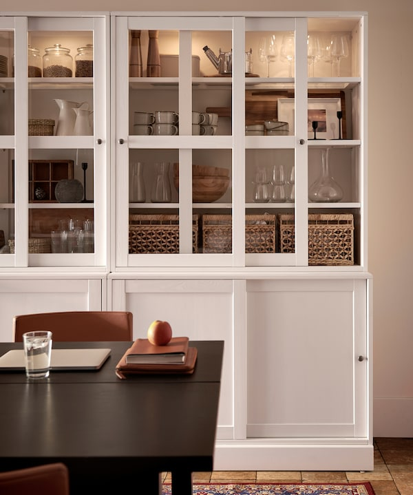 Two white glass-doors cabinets with integrated lighting, storage boxes, decorative items and dinnerware stored inside.