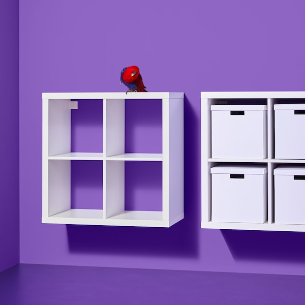 Two white KALLAX shelving units, one containing white boxes, are mounted side by side on a purple wall.