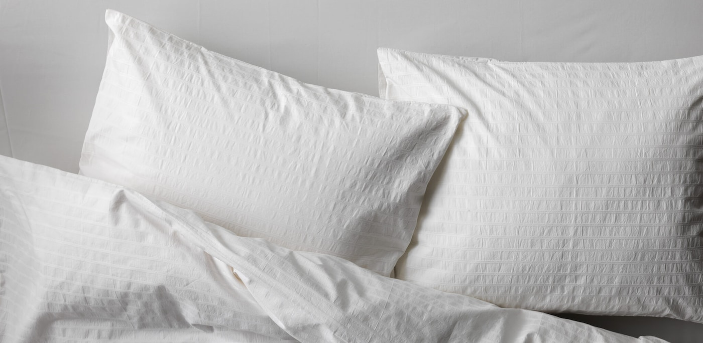 Two white pillows on a bed with a white comforter