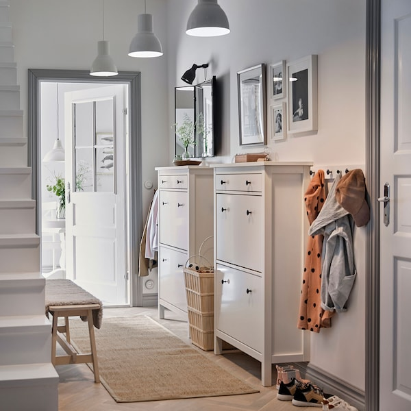 Two white shoe cabinets in a hallway.