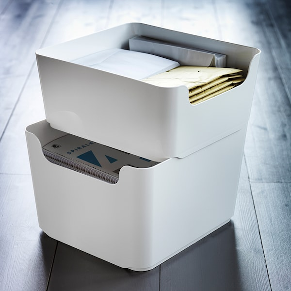 Two white, stacked waste bins filled with paper