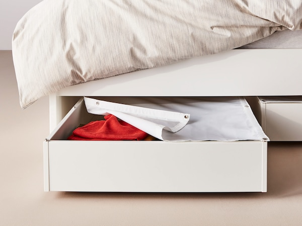 Two white under bed storage boxes, one pulled out with lid partially open, revealing red fabric.
