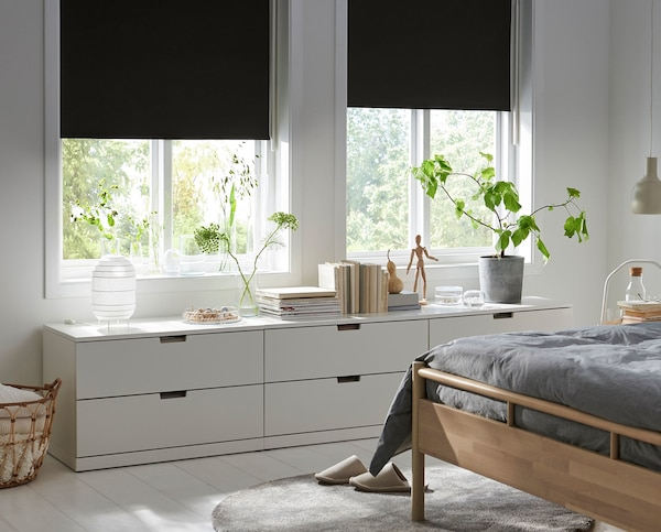 Two windows in a bedroom with blinds and a side cabinet for storage.