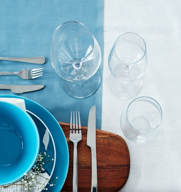 Two wine glasses and a water glass are arranged at a setting.