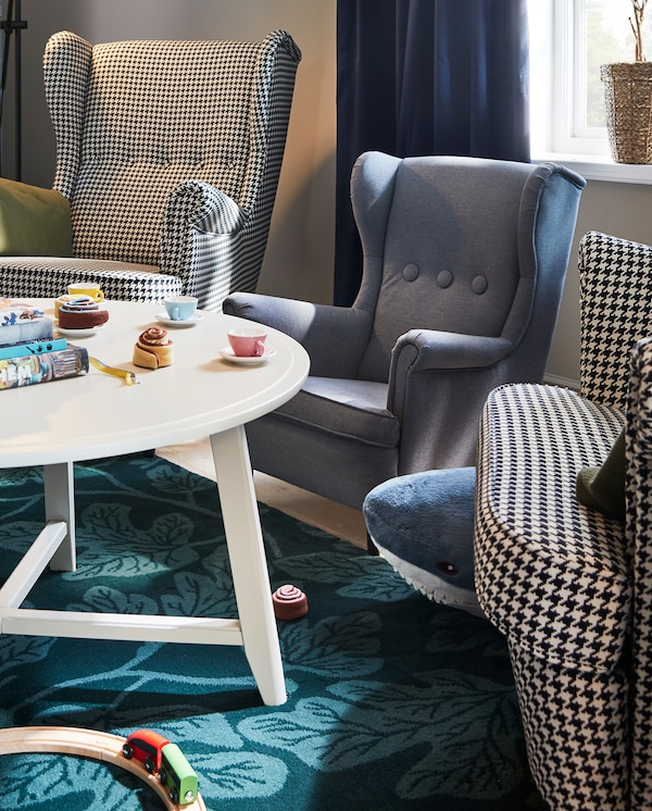 Two wing chairs and a miniature children's armchair stand by a white round KRAGSTA table with toys on it.
