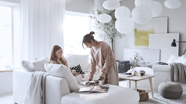 Two women browsing a catalog on a sofa.