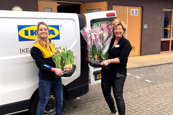 Two women carrying orchid and tulip plants are standing next to an IKEA delivery vehicle. They appear to be very happy.