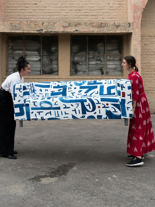 Two women holding either end of a sofa with a blue and white textile design on a tarmac surface outside a brick storehouse.