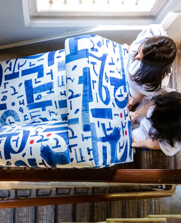 Two women in a stairwell next to a window holding the end of a blue and white fabric sofa they are carrying.