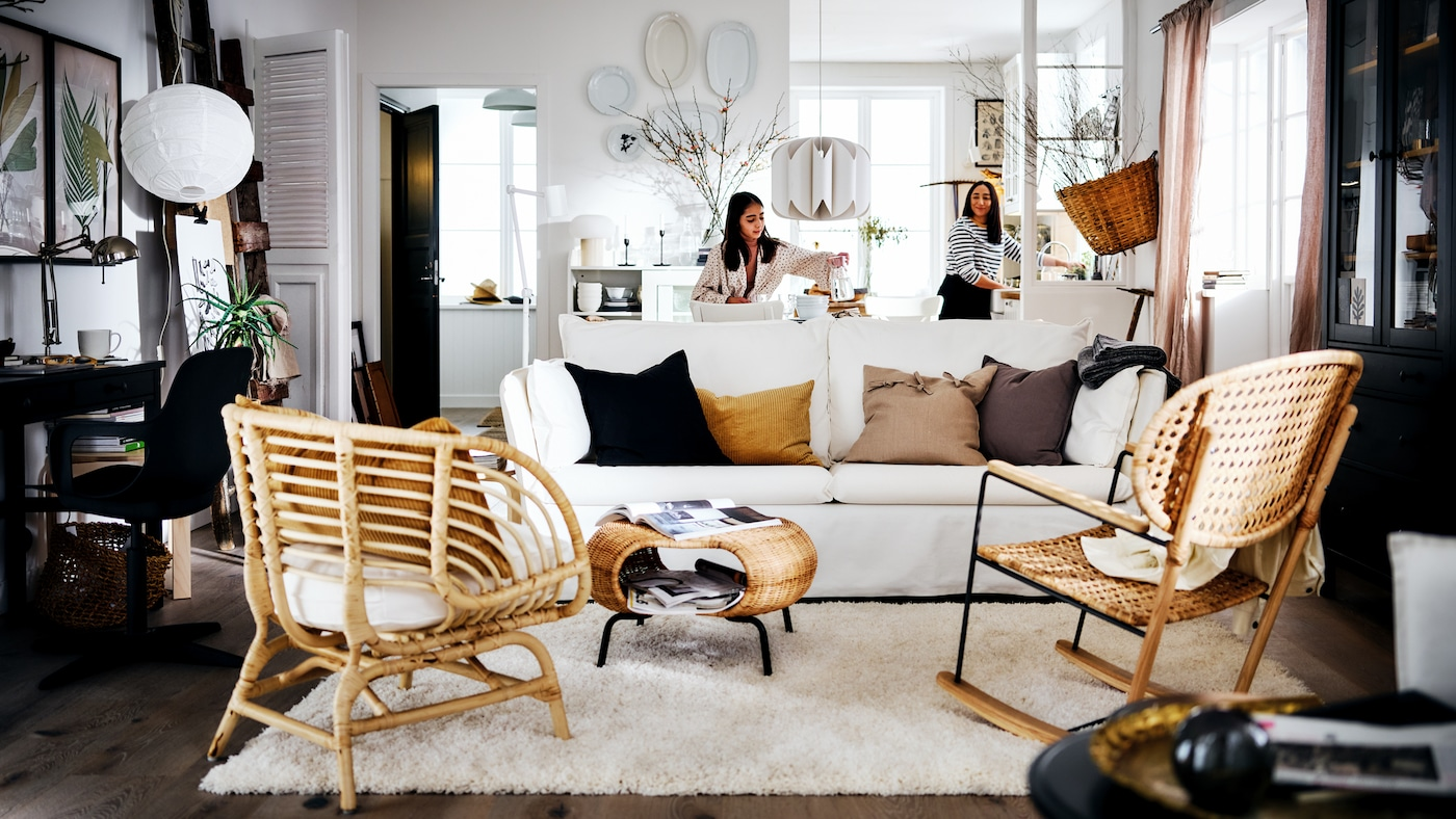 Two women in a white country-style living area with a white BACKSÄLEN sofa in front of a rug and two rattan armchairs.
