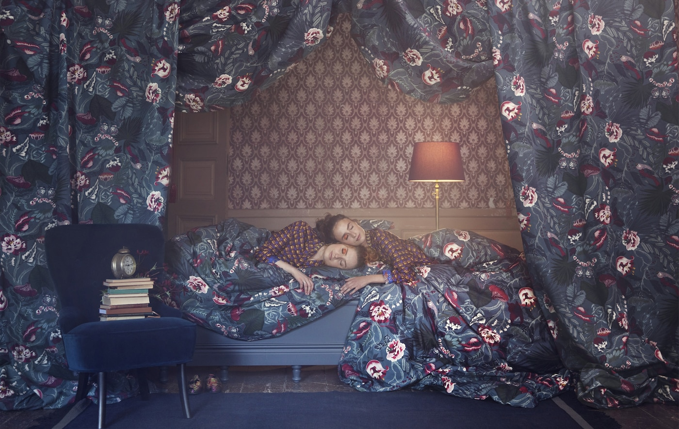 Two women laying on a bed with patterned wallpaper surrounded by floral fabric.