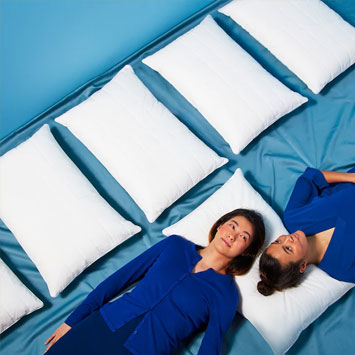 Two women laying on the same pillow against a blue background