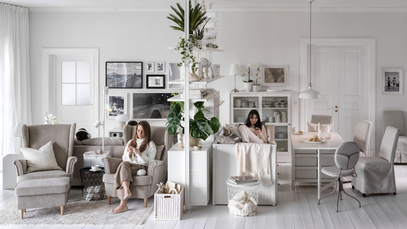 Two women seated, one in a beige STRANDMON armchair, on either side of an ELVARLI storage unit in a large, light living room.